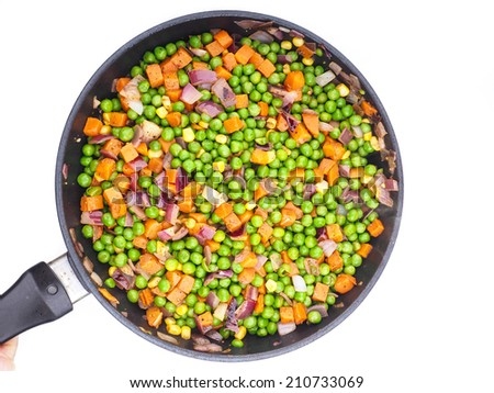 Fry pan isolated towards white background with peas, corn, carrots and red onion - stock photo