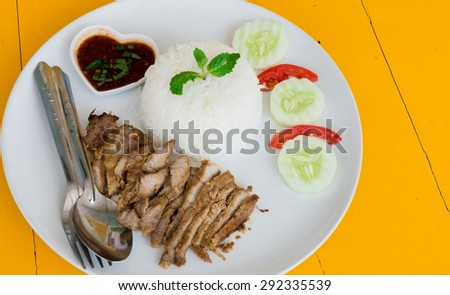 Fry pork.Fry pork chop into pieces with rice cucumber tomato and spicy sauce on yellow table. select focus - stock photo