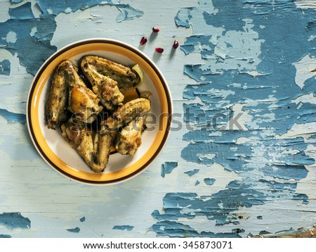 Fryed chicken wings on plate on old weathering painted table - stock photo