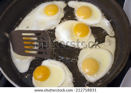 Frying a batch of eggs for breakfast in a non-stick frying pan using a spatula, close up high angle view - stock photo