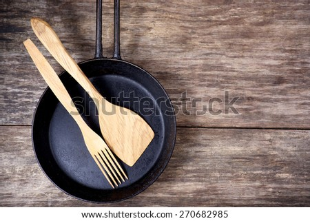 Frying pan and kitchen utensils on wooden table background - stock photo