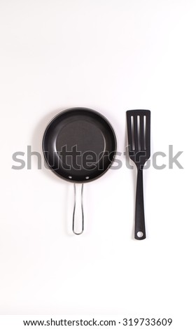 frying pan and spatula with copyspace isolated on white background