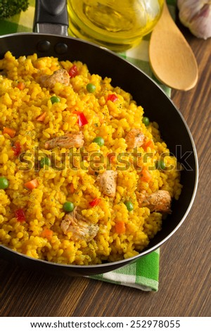frying pan full of rice on wooden background - stock photo