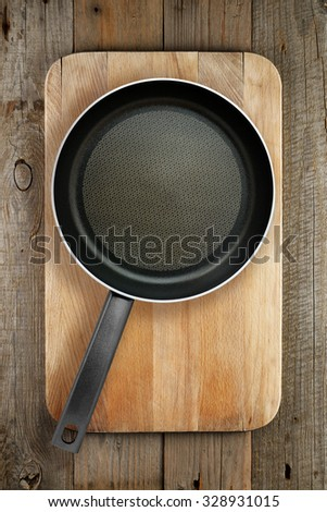 Frying pan on wooden chopping board top view - stock photo