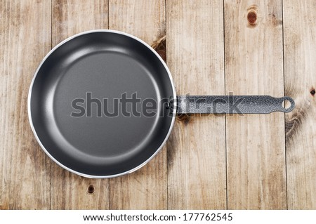 Frying pan on wooden table background. View from above - stock photo