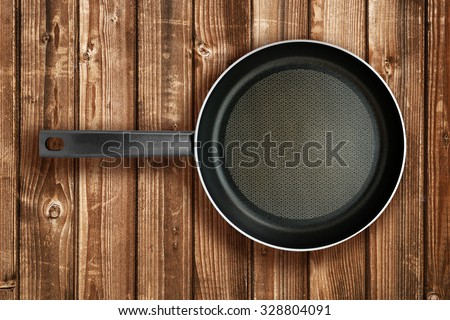Frying pan on wooden table top view - stock photo