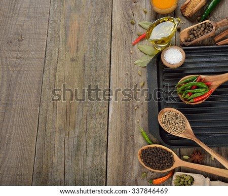 Frying pan, spices and seasonings on a wooden background