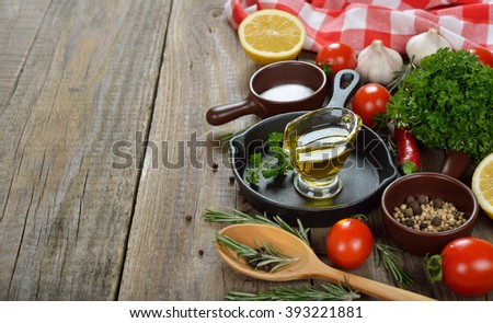 Frying pan, spices and seasonings on a wooden background - stock photo