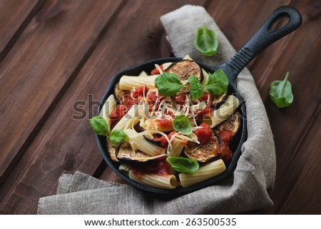 Frying pan with pasta alla Norma over rustic wooden background - stock photo