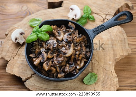 Frying pan with roasted champignons, rustic wooden background - stock photo