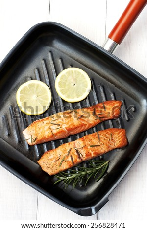 Frying pan with two salmon steaks and herbs  - stock photo