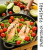 Frying pan with two salmon steaks, stir-fry veggies and herbs, Shallow dof. - stock photo