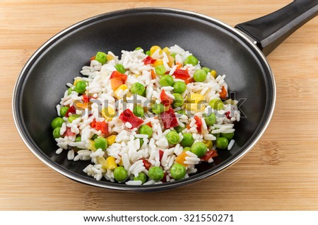 Frying pan with vegetable mix on wooden board