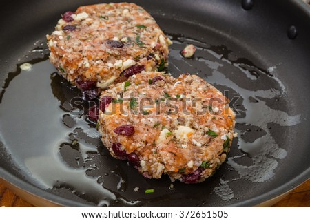 Frying salmon burger stuffed with cranberries and gorgonzola cheese.