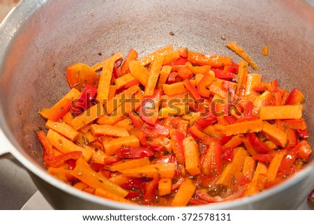 Frying sweet pepper and carrots in iron cast pot - stock photo