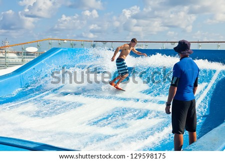 FT. LAUDERDALE, FL - JAN. 12:  Man surfing on the Flow Rider aboard the Oasis of the Seas on Jan. 12, 2013..  Royal Caribbean offers this activity to all it's guests aboard it's Oasis-class ships. - stock photo