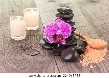 Fuchsia Moth orchid, black stones and candles on weathered deck close up - stock photo