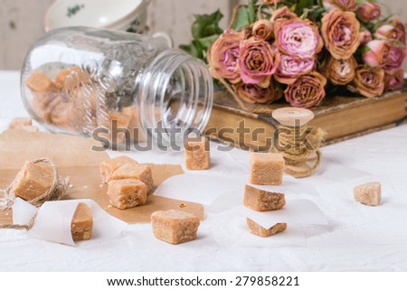 Fudge candy and caramel on baking paper and in glass jar, served over white tablecloth with bouquet of dry pink roses and thread for gift making. See series - stock photo