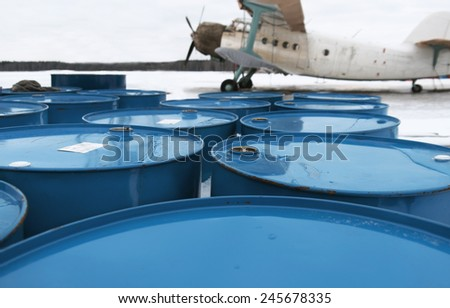 Fue lbarrels stacked on the ground at an airport, retro aeroplane in the background - stock photo