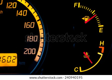 Fuel gauge and temperature gauge with a yellow glowing dial. Tank is almost half full and the engine is at ideal running temperature. Isolated against a black background. - stock photo