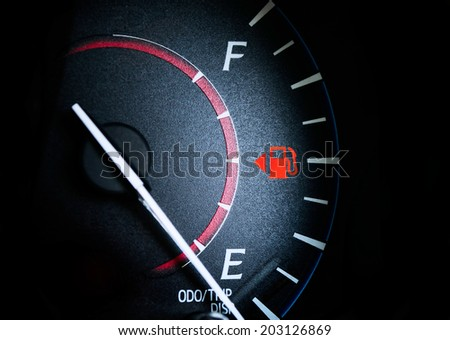 Fuel Gauge Showing Almost Empty,Time for another very expensive fuel purchase. Red warning icon light door. - stock photo