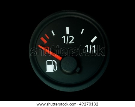Fuel gauge with a red needle  indicating empty on car dashboard isolated on black