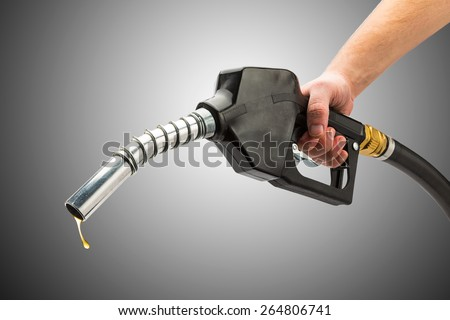 fuel glass with pump nozzle and a golden petrol drop - stock photo