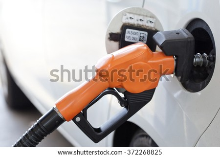 Fuel nozzle add fuel in car at gas station