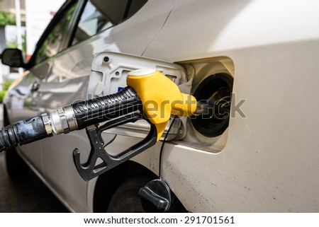 Fuel nozzle during refueling at a gas station.