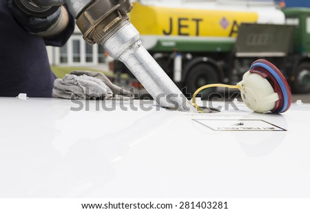 Fuel nozzle filling up aircraft, refueling jet fuel in an aircraft wing, Focused on refueling gun. Focused on refueling gun  - stock photo
