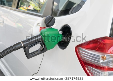 Fuel nozzle to add fuel in car at gas station - stock photo