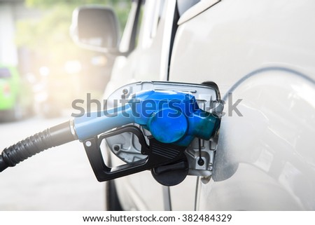 Fuel nozzle to refill fuel in car at gas station.