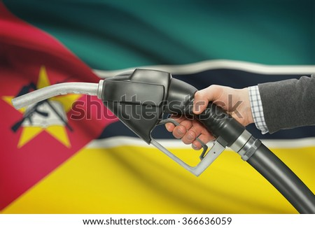 Fuel pump nozzle in hand with flag on background - Mozambique - stock photo