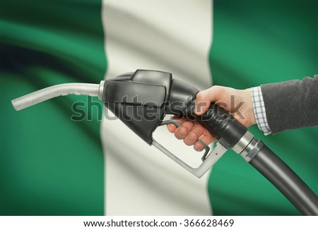 Fuel pump nozzle in hand with flag on background - Nigeria - stock photo