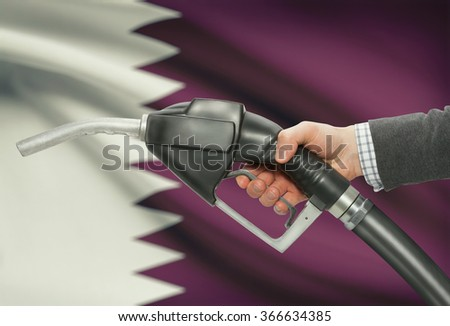 Fuel pump nozzle in hand with flag on background - Qatar - stock photo