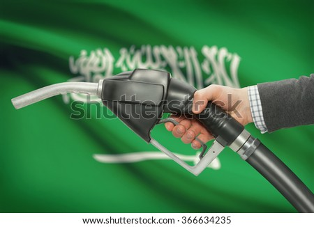 Fuel pump nozzle in hand with flag on background - Saudi Arabia - stock photo