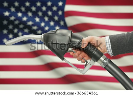 Fuel pump nozzle in hand with flag on background - United States - USA - stock photo