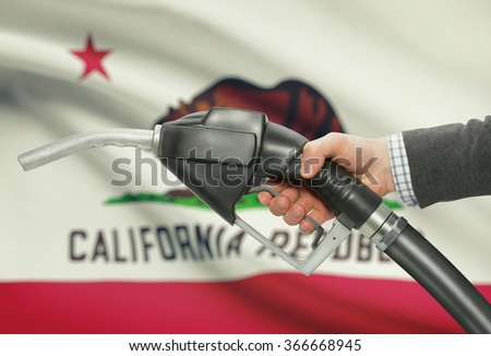 Fuel pump nozzle in hand with US states flags on background - California - stock photo