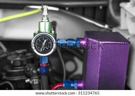Fuel regulator gage with aluminium spare tank on racing car engine - stock photo