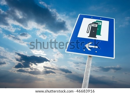 Fuel station sign against cloudy sky - stock photo