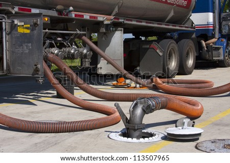 Fuel tanker diesel pumping fuel into filling station underground tank - stock photo