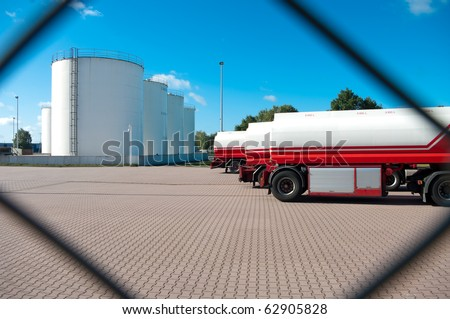 fuel tanks seen from behind a fence - stock photo