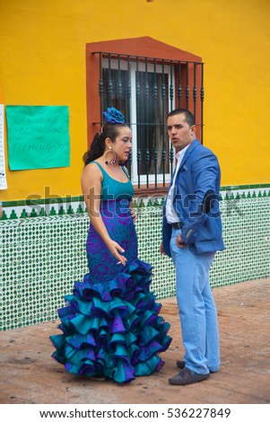 Fuengirola, Spain - October 10, 2014: Young couple dressed in blue clothes styled as traditional Andalusian clothing at annual fair in Fuengirola.