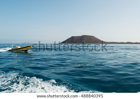 Fuerteventura: a man on a dinghy with the Caldera mountain on Lobos Island on September 4, 2016. Caldera is the volcano of Lobos, a small island located just 2 kilometers north of Fuerteventura
