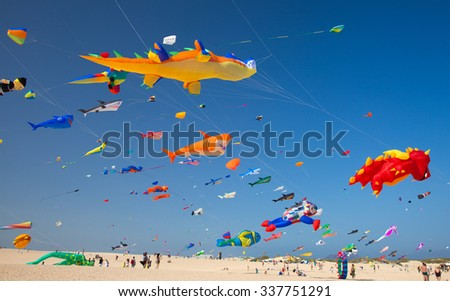 FUERTEVENTURA, SPAIN - NOVEMBER 8: Viewers watch from the ground as colorful kites fill the sky at 28th International Kite Festival, November 8, 2015  in Dunes of Corralejo, Fuerteventura, Spain - stock photo