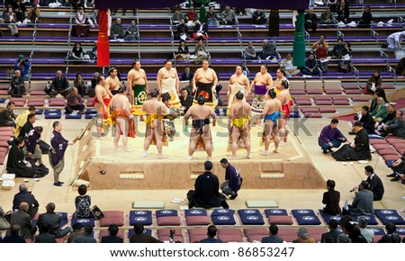 FUKUOKA, JAPAN - NOVEMBER 17: Sumo wrestlers gather around the referee at a Grand Sumo tournament on November 17, 2010 in Fukuoka, Japan. There are six official tournaments held each year in Japan. - stock photo