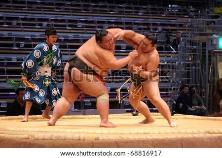 FUKUOKA, JAPAN - NOVEMBER 19: Unidentified Sumo wrestlers engaging in the arena of the Fukuoka Tournament on November 19, 2010 in Fukuoka, Japan. - stock photo