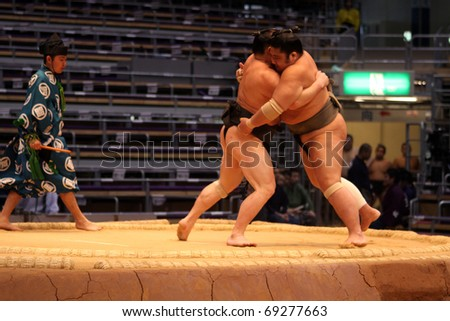 FUKUOKA, JAPAN - NOVEMBER 19: Unidentified sumo wrestlers lifting each other out of the ring in the Fukuoka Tournament on November 19, 2010 in Fukuoka, Japan. - stock photo