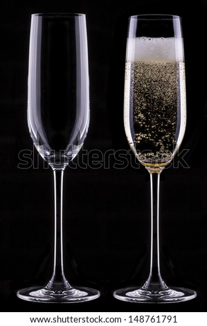 full and empty glass of champagne isolated on black background