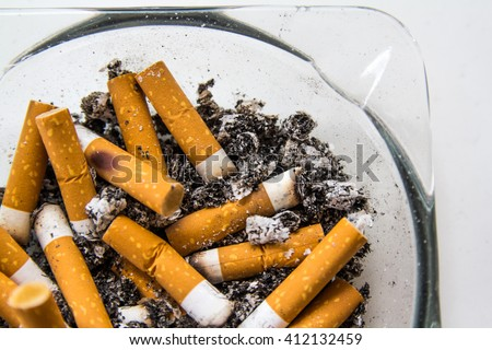 Full ashtray with smoked cigarettes and lot of ashes on white table - stock photo